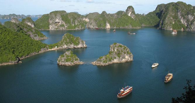 Lime karst scenery and junks cruising on Halong Bay, Vietnam