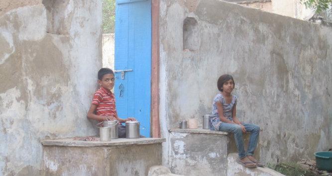 Village children sitting on a wall, Alsisar, India