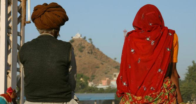 Locals sitting on a fence, Pushkar, India
