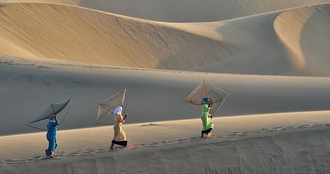 Colourful ladies crossing the dunes, Phan Thiet, Vietnam