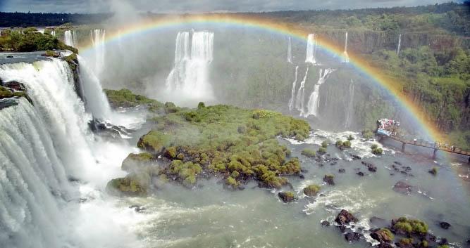 A rainbow shimmers over the Iguassu Falls, Brazil